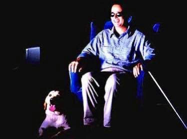 Photo shows a man, wearing dark glasses, and a dog in a darkened room watching tv